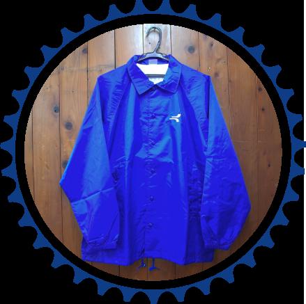年月の趣を感じる木目の壁にかかった鮮やかな青色の作業用上着